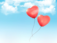 Two heart-shaped balloons floating in the sky